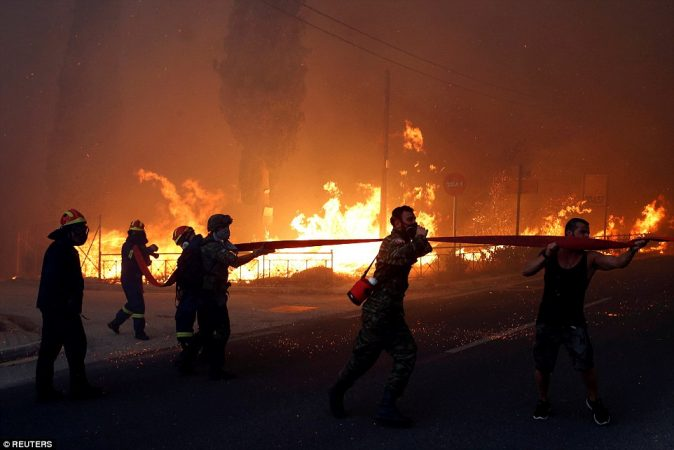 4E8540F400000578-5984481-Firefighters_soldiers_and_local_residents_carry_a_hose_as_a_wild-a-4_1532412461892-2-674x450