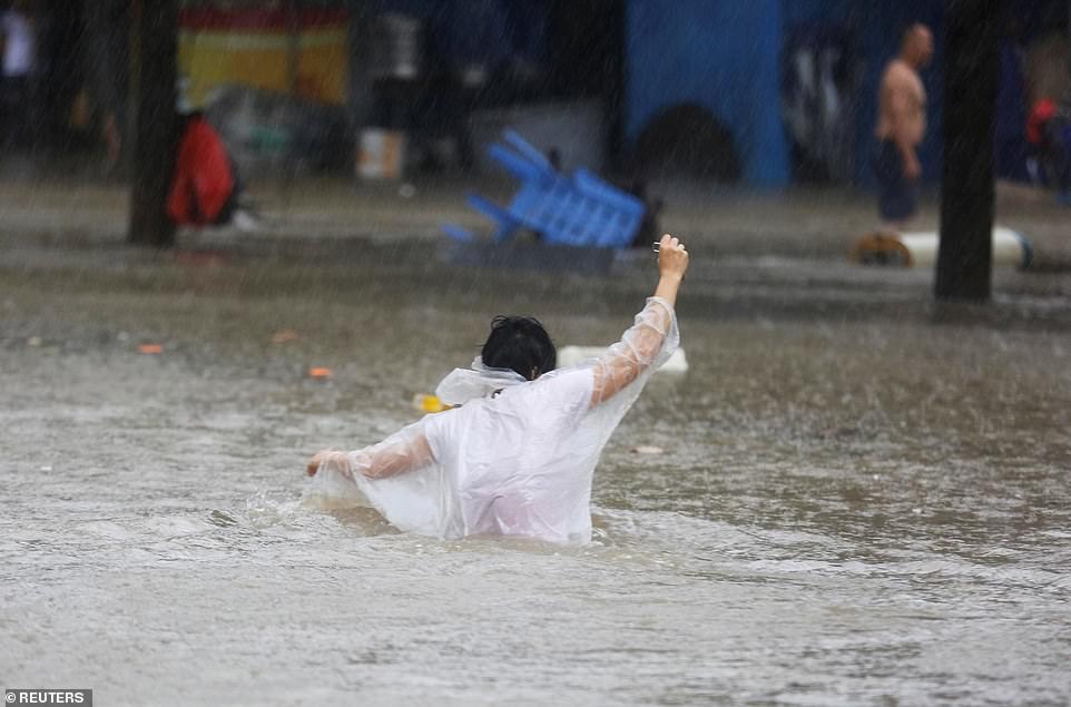 Pedestrian wades through waist-high floodwaters on a street amid heavy rainfall as Typhoon Mangkhut hits Zhongshan, Guangdong